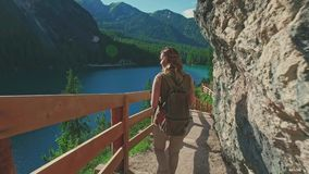 Woman hiker walking around the Braies lake and enjoys his spectacular sceneries, Dolomites, Italy stock video
