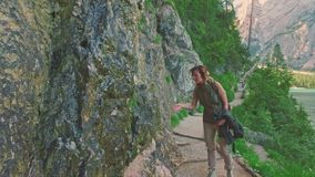Woman hiker walking around the Braies lake and enjoys his spectacular sceneries, Dolomites, Italy stock video footage