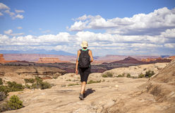 Woman hiker walking with backpack in mountains. Stock Photo