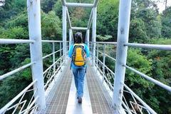 Woman hiker walking at bridge in mountain peak Stock Photos