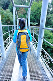 Woman hiker walking at bridge in mountain peak Royalty Free Stock Photography