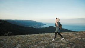 Woman hiker walking on mountain terrain wearing backpack stock video