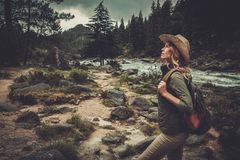Woman hiker walking near wild mountain river. Stock Images