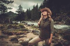 Woman hiker walking near wild mountain river. Stock Photos