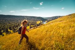 Woman hiker walks on the hill. With mountain on the horizon. Ural Mountains, Russia royalty free stock photo