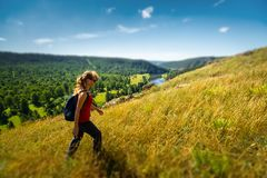 Woman hiker walks on the hill. Ural Mountains, Russia. Tilt shift effect applied stock image