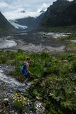 Woman hiker. Walks in the valley with lush vegetation and glacier on the horizon royalty free stock image