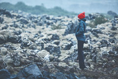 Woman hiker walks on volcanic Lava fields on background of mountains of Iceland. Stock Photo