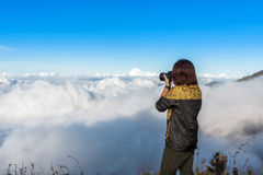 Woman hiker wear jacket, taking photograph, enjoy and happy with mountain top view after finished climbing at mount Rinjani. Woman hiker wear yellow and black Royalty Free Stock Images