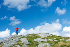 Woman hiker on wild nature. Remote view of happy excited woman hiker standing on wild nature of Norway with raised hands waving Stock Photo