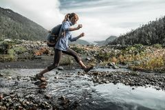 Woman hiker. Woman crossing the river in the wild valley royalty free stock photos