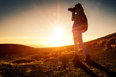 Woman hiker. With backpack takes picture of the landscape in mountains during golden hour stock photos