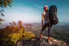 Woman hiker. With big backpack stands on the rock and enjoys the valley view stock image