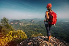 Woman hiker. Stands on the cliff with backpack and watches the walley royalty free stock image