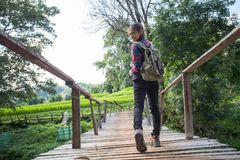 Woman hikers shoes. Female tourists walk along the bridge over the river stock photo