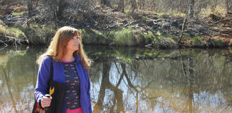 A Woman Hikes Along a Creek in the Sun Stock Image