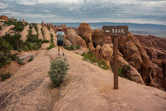 Woman Hikes Down Slickrock in Arches National Park Stock Image