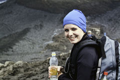 A woman hiking. A woman taking a break from hiking in Iceland. Holding a water bottle and smiling towards the camera stock photos