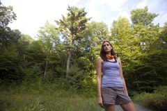 Woman Hiking. Twenty year old woman pauses in a meadow on hike through woods royalty free stock photography