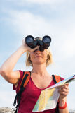 Woman hiking. Young blonde woman hiking watching through binoculars. Copy space Stock Images