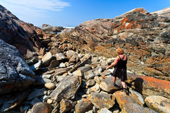 Woman hiking along the Rocky coastline Royalty Free Stock Photos