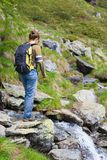 Woman hiking in the Alps, crossing little stream Royalty Free Stock Photography