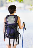 Woman hiking with backpack and walking stick Stock Images