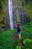 Woman hiking Backpack waterfall. Woman looks at amazing waterfall after long hike royalty free stock image