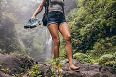 Woman hiking barefoot on forest trail. Low angle view of young woman walking down the mountain barefoot. Female hiker walking barefoot on rock with waterfall in Stock Photo