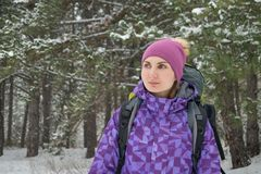 Woman Hiking with Big Backpack in Beautiful Winter Forest Stock Photo