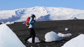 Woman hiking on black sand iceberg beach stock video footage