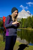 Woman while hiking checking map on cell phone Royalty Free Stock Photography