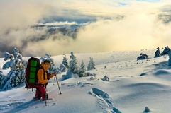 Woman hiking in deep snow. Woman hiking in winter mountains, surrounded by clouds Royalty Free Stock Photos