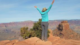 Woman Hiking In Grand Canyon Is Coming To The Observation Point And Arms Up. Tourist woman hiking trail in Grand Canyon national Park in Arizona USA, is coming stock video footage