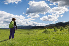 Woman hiking in a green field Royalty Free Stock Photography
