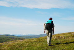 Woman hiking between green hills and the blue sky. Royalty Free Stock Image