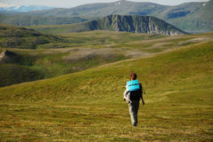 Woman hiking in green mountains of summer Soroya. Royalty Free Stock Photos