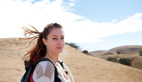 Woman hiking while looking at the camera. On a sunny day Stock Photo
