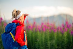 Woman hiking in mountains, adventure and travel. Woman hiking and walking in mountains with backpack. Looking at beautiful view. Travel and trekking in summer Stock Image