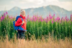 Woman hiking in mountains, adventure and travel. Woman hiking and walking in mountains with backpack. Looking at beautiful view. Travel and trekking in summer Stock Images