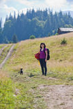 Woman hiking in mountains with dog Stock Image