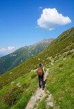 Woman hiking in the mountains on a tourist track Royalty Free Stock Image