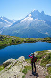 Woman hiking in the mountains on a tourist track Stock Photos