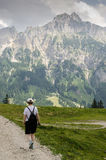Woman is hiking in the mountains. Woman is hiking on a trail in the mountains Stock Photography