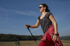 Woman Hiking Nordic Walking. Low angle view of a woman using ski poles to hike in the summer. Horizontal shot Stock Photography
