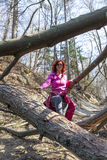Woman hiking over a fallen tree trunks Royalty Free Stock Photos