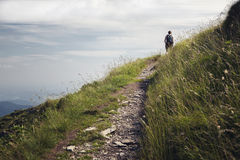 Woman on hiking path. Woman walking on a hiking path in the swiss alps Stock Image