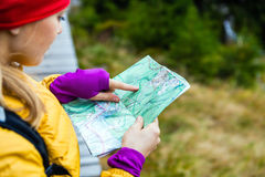 Woman hiking and reading map in forest Stock Photo