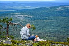 Woman hiking. Woman sitting and eating snacks on hiking trail Stock Image