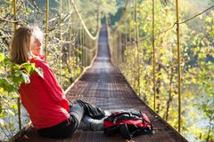 Woman hiking sitting in suspension bridge Royalty Free Stock Photo